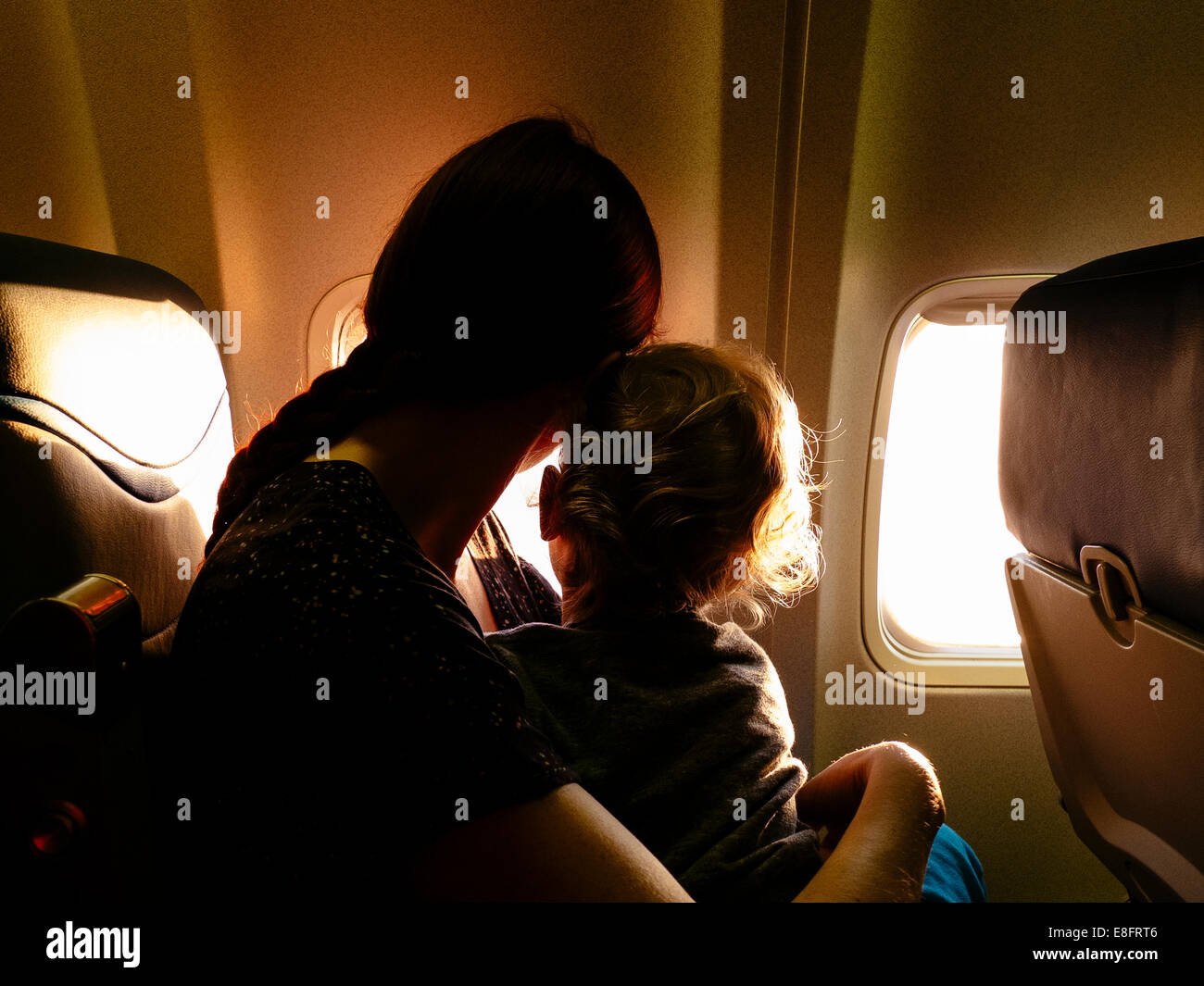 Mother and son looking out of airplane window Stock Photo