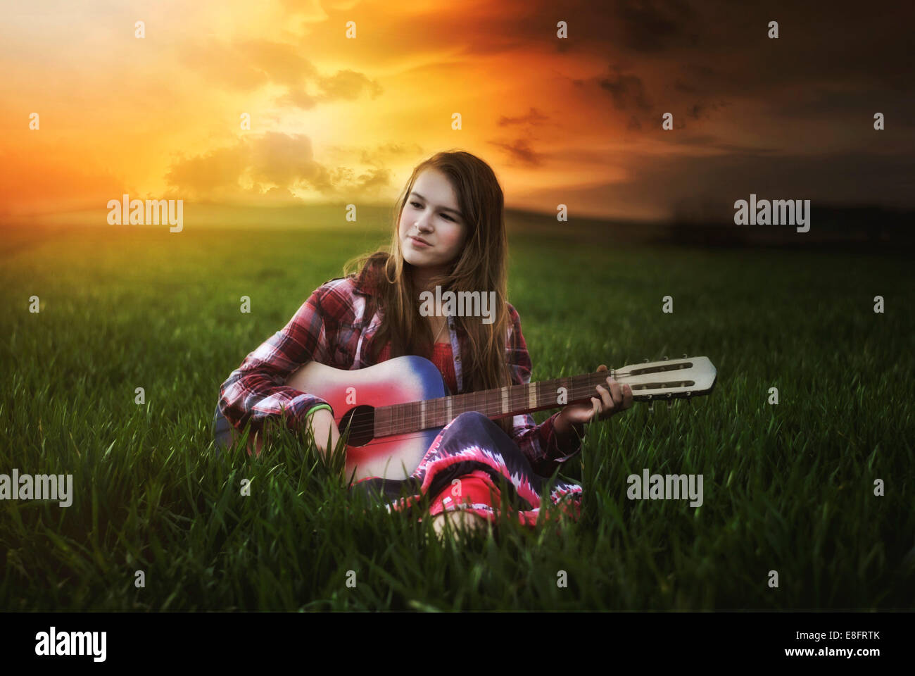 Girl sitting in field at sunset playing guitar - Stock Image