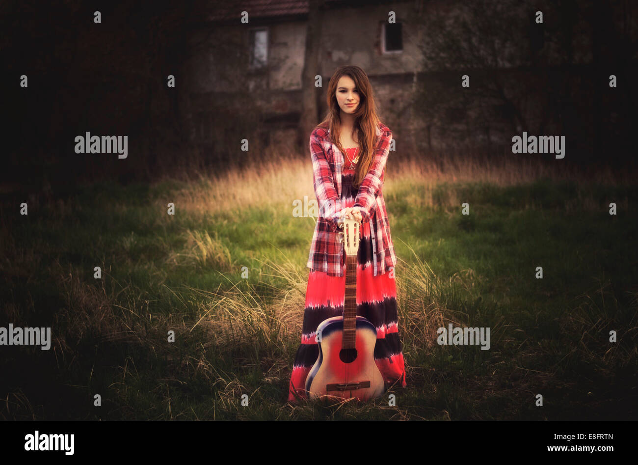 Girl standing with guitar - Stock Image