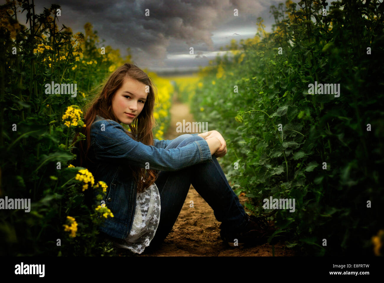 Side view of girl sitting in field - Stock Image