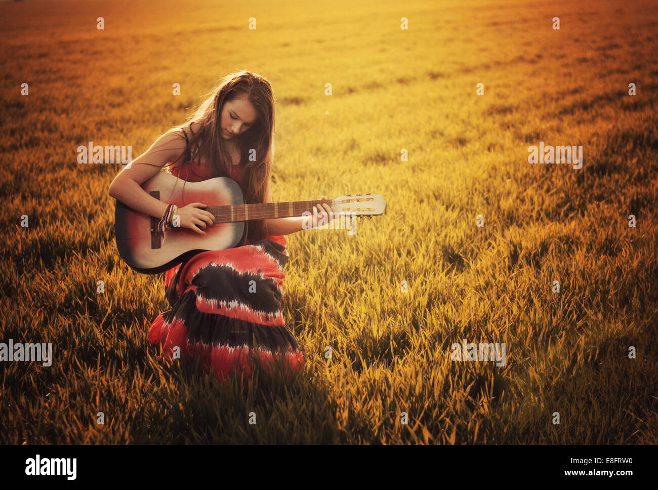 Girl sitting in field playing guitar - Stock Image