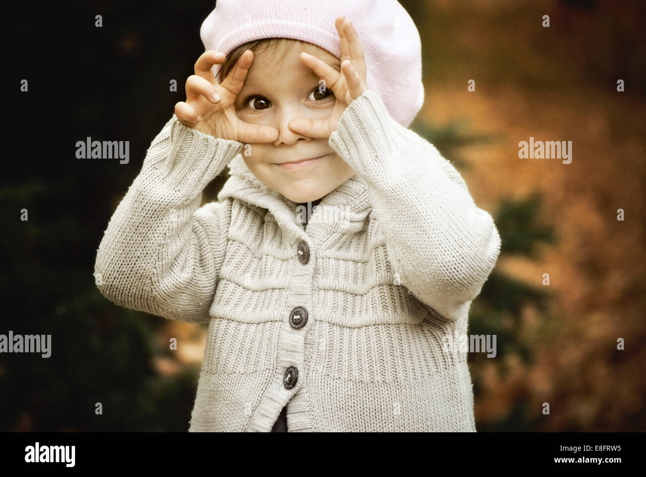 Child framing face with hands - Stock Image