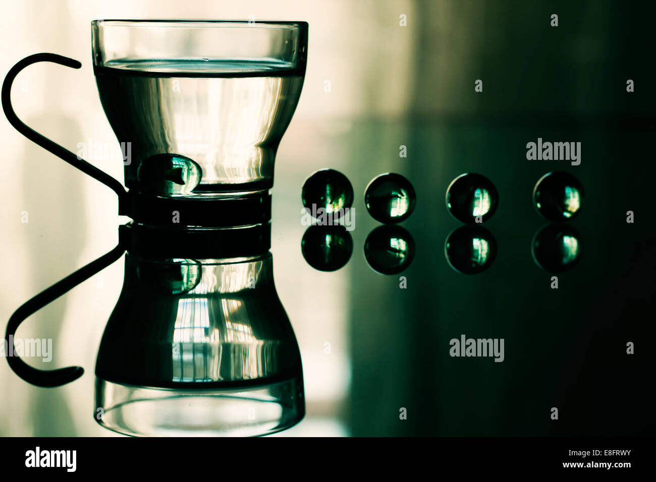 Glass cup with water and marbles - Stock Image