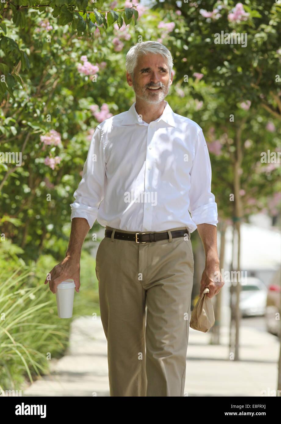 Businessman walking down street - Stock Image