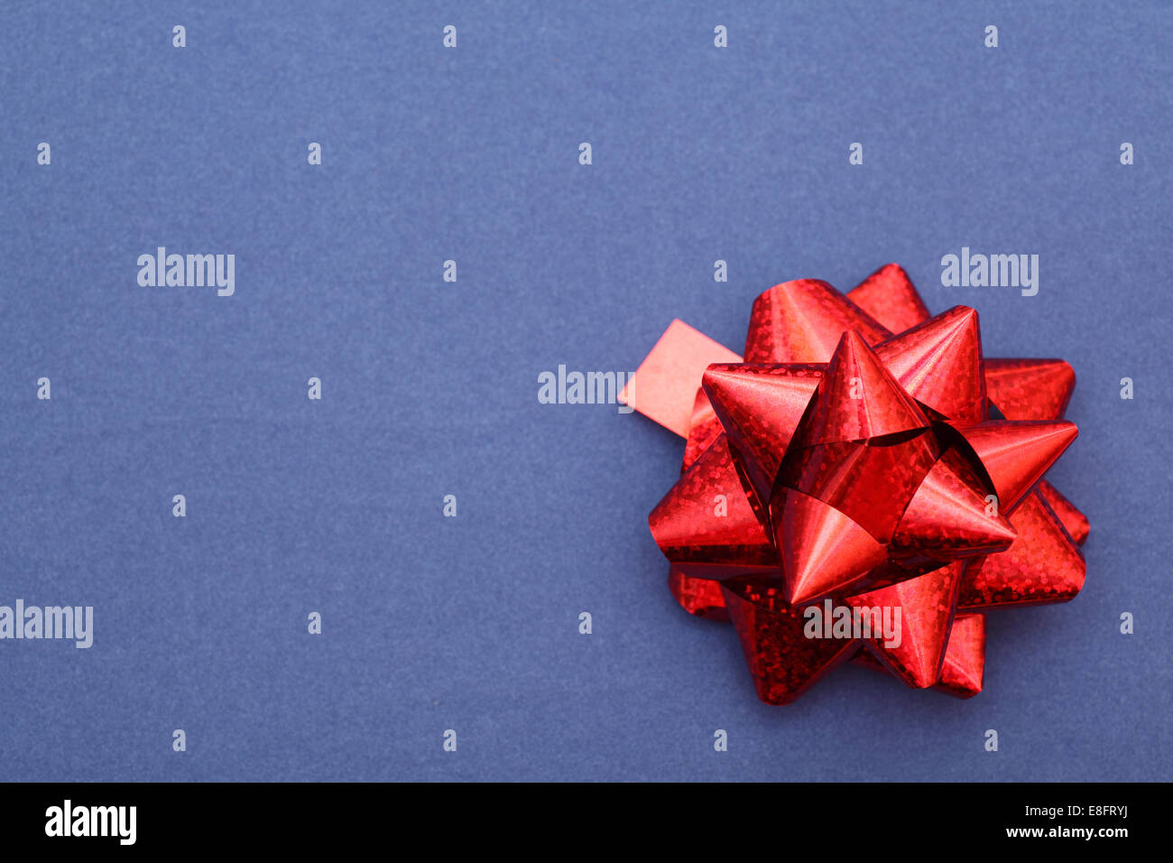 Red bow on blue paper background. Closeup. - Stock Image