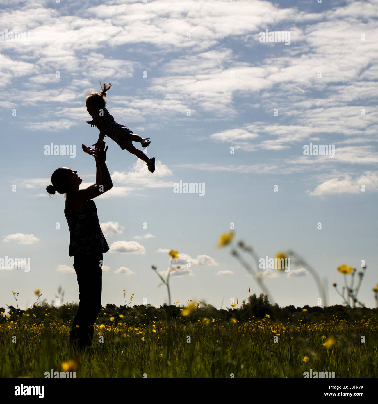 Silhouette of mother throwing son in air - Stock Image