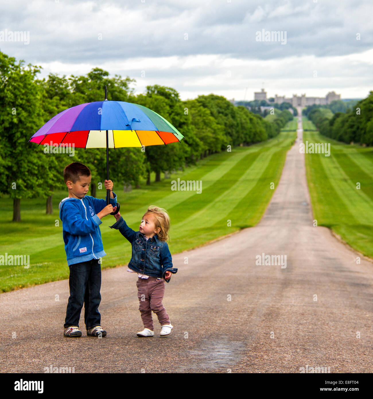 UK, Two boys playing with umbrella at Windsor Great Park - Stock Image