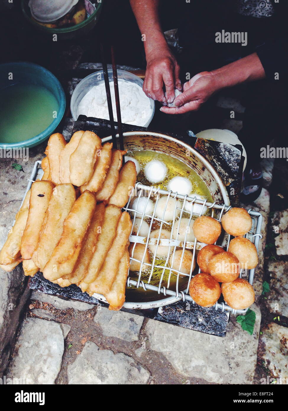 Vietnam, Lao Cai Province, Sa Pa, Woman frying dough on the street - Stock Image