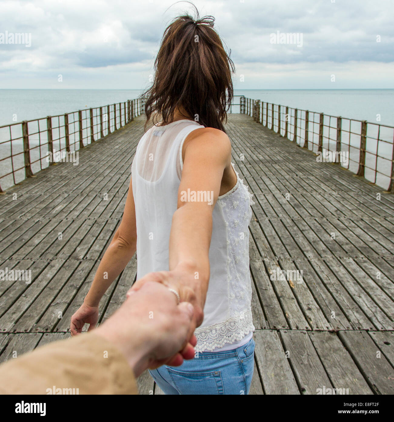 UK, Woman holing man's hand on pier - Stock Image