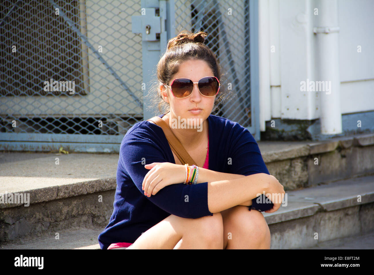 Woman wearing sunglasses sitting on a step - Stock Image