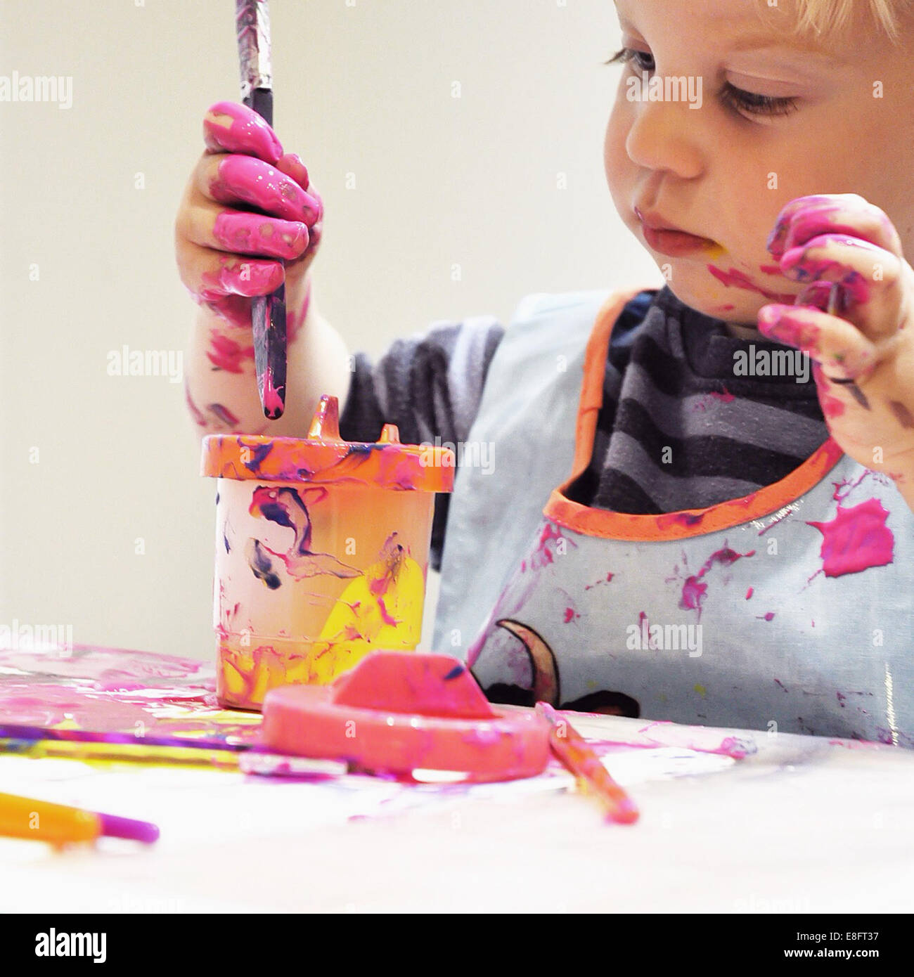 Boy making a mess while painting - Stock Image