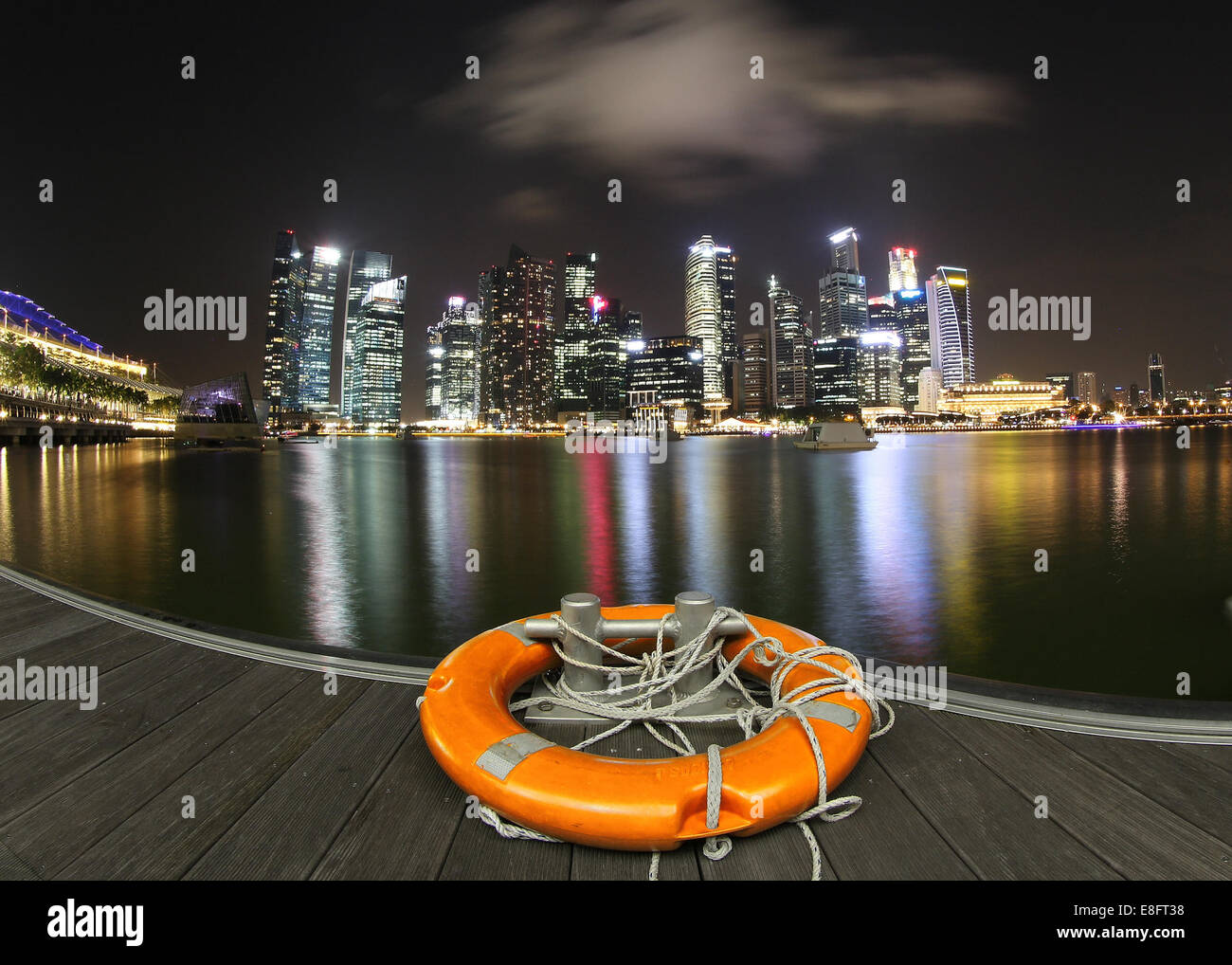 City skyline at night with lifebelt on dock, Marina Bay, Singapore - Stock Image