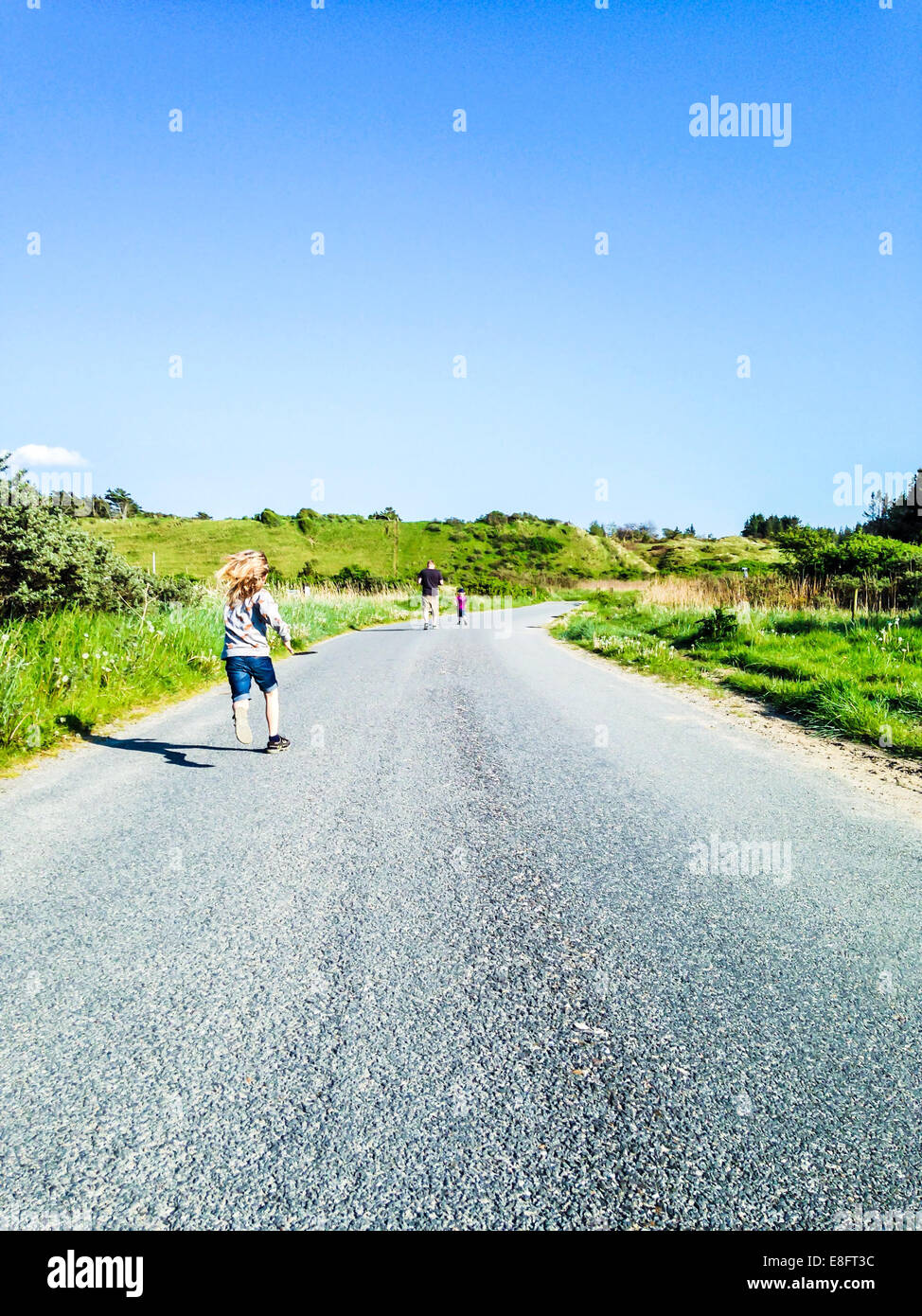 Rear view of Man running down road with two sons, Denmark - Stock Image