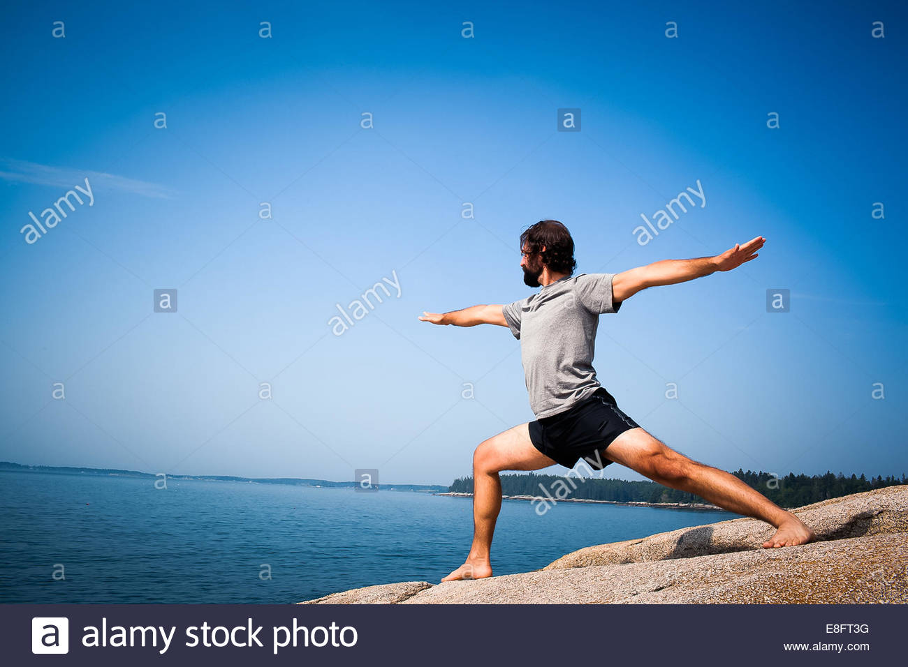 Man doing warrior yoga pose on beach, Maine, America, USA - Stock Image