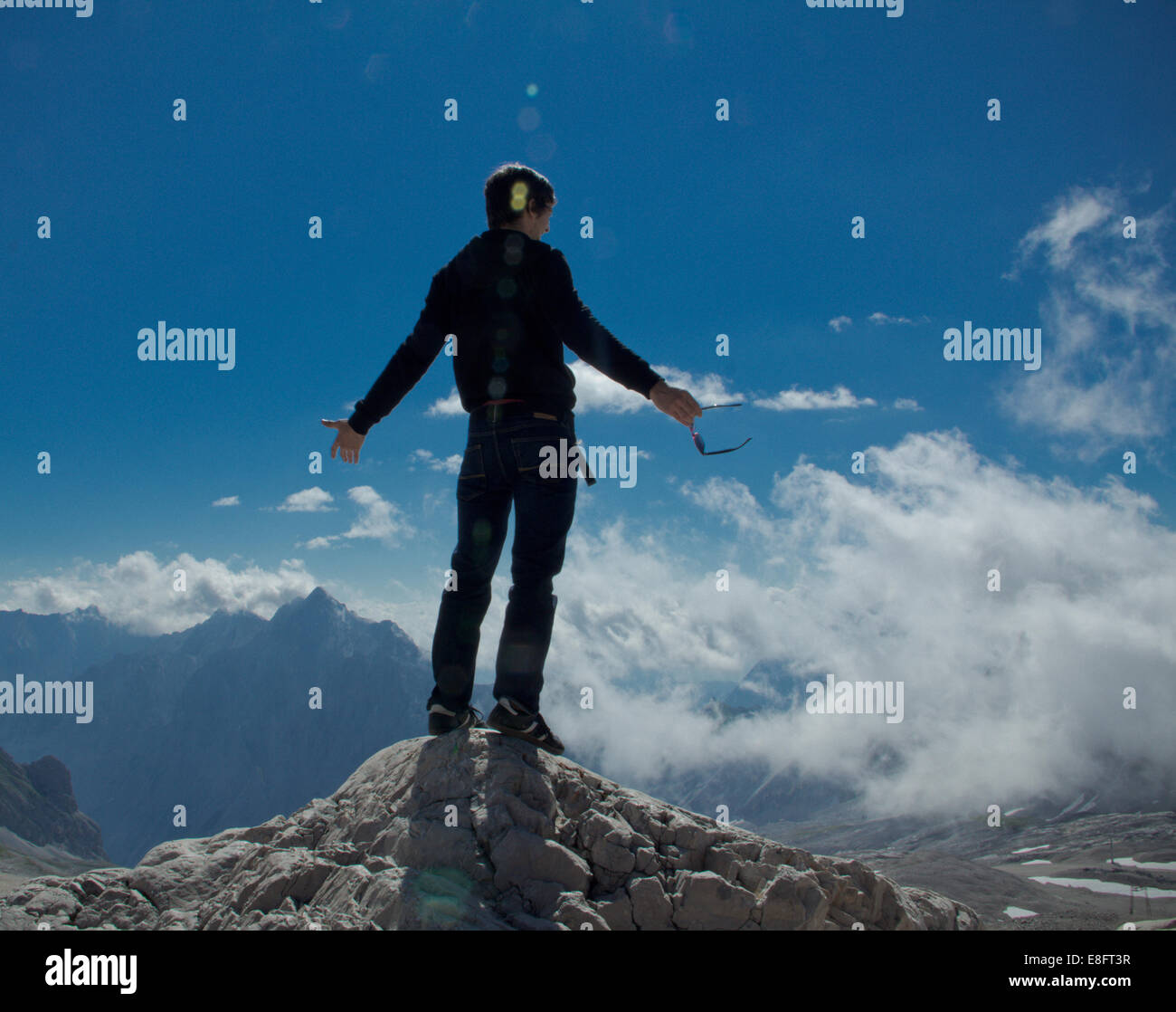 Man standing on the top of a mountain - Stock Image