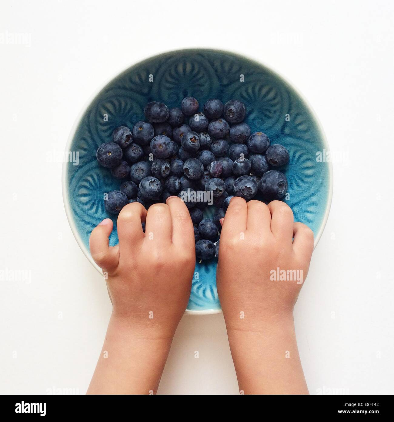 Boy's hands in a bowl of blueberries - Stock Image
