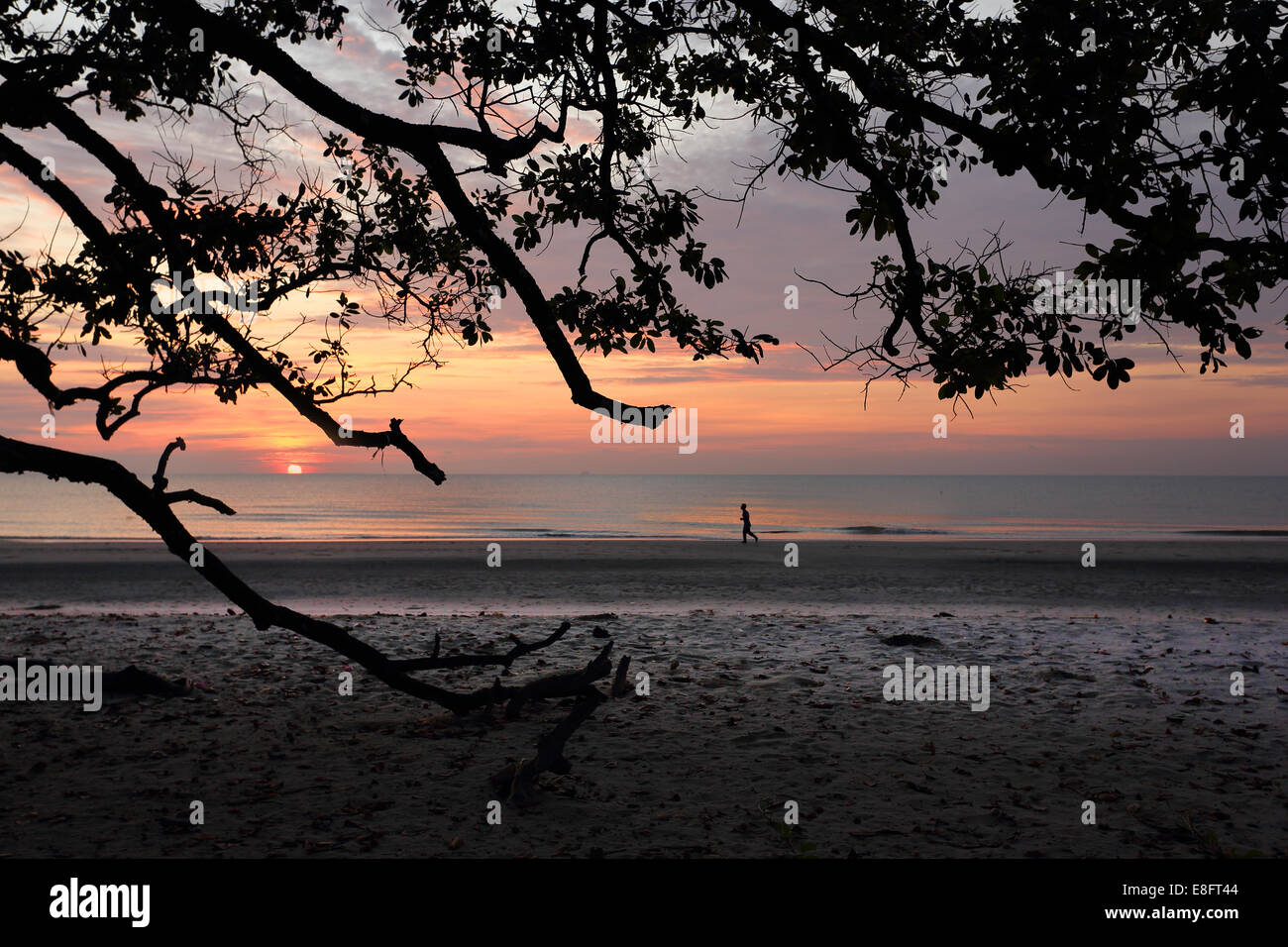 A silhouetted man running at beach during twilight - Stock Image