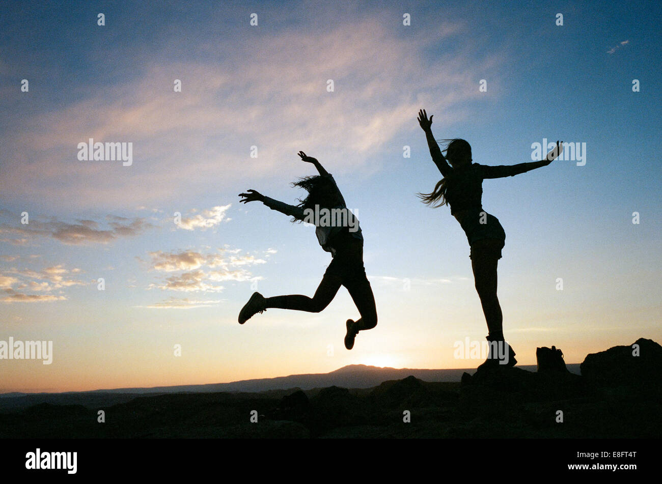 Silhouettes of two women jumping at sunset - Stock Image