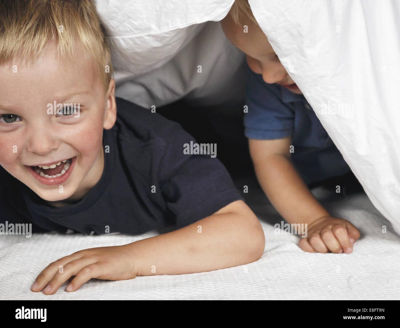 Two boys hiding under duvet - Stock Image
