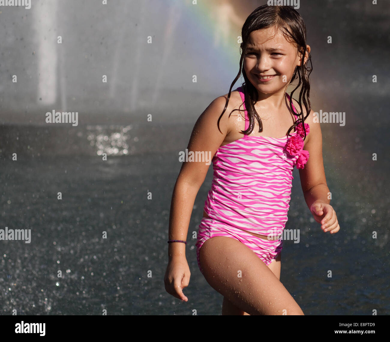 Girl wearing swimsuit standing in front of water fountain - Stock Image