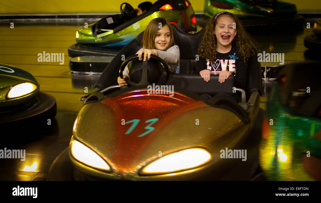 Two girls in bumper cars at a fairground - Stock Image