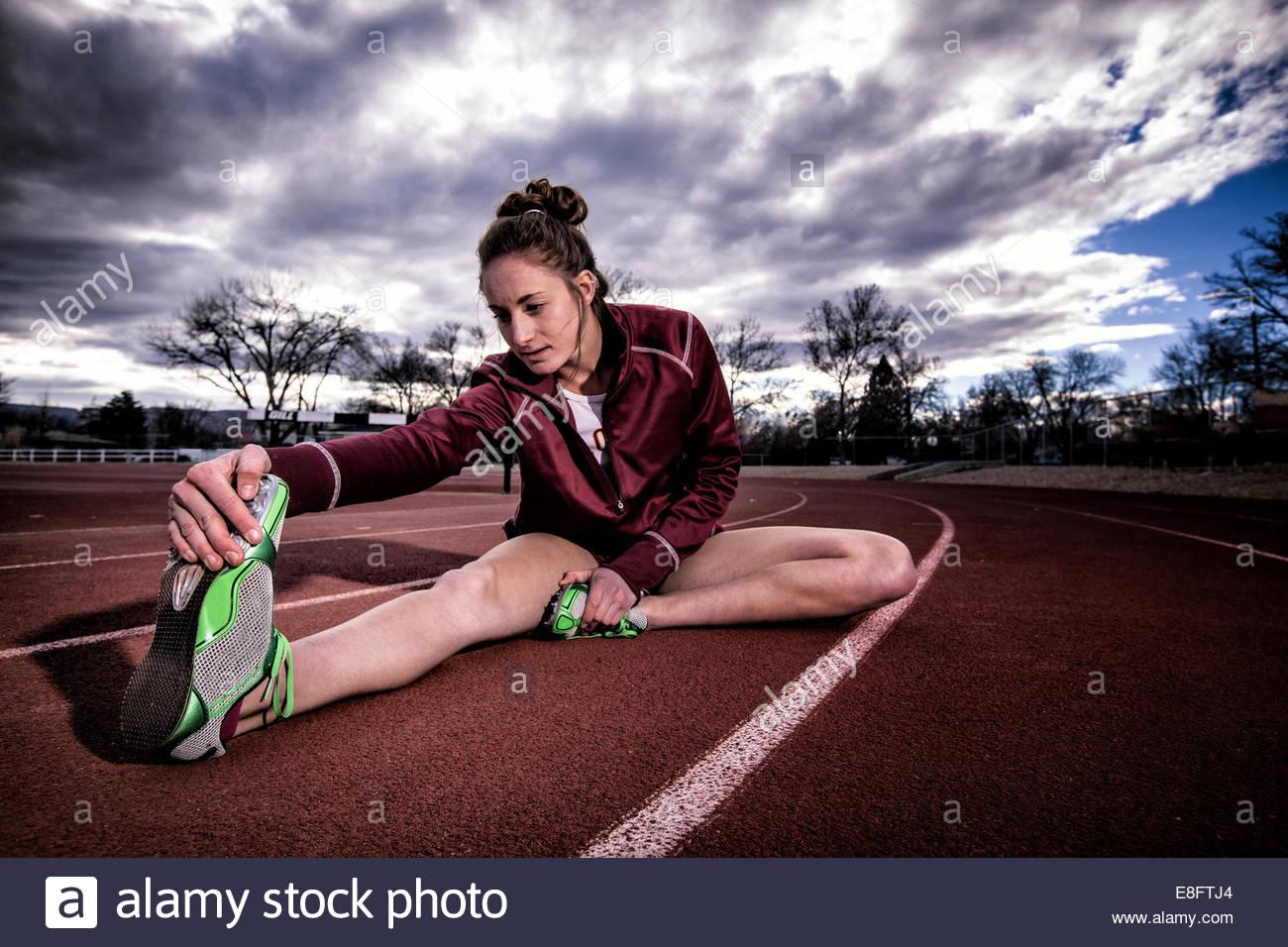 Female runner sitting on running track stretching, Colorado, America, USA - Stock Image