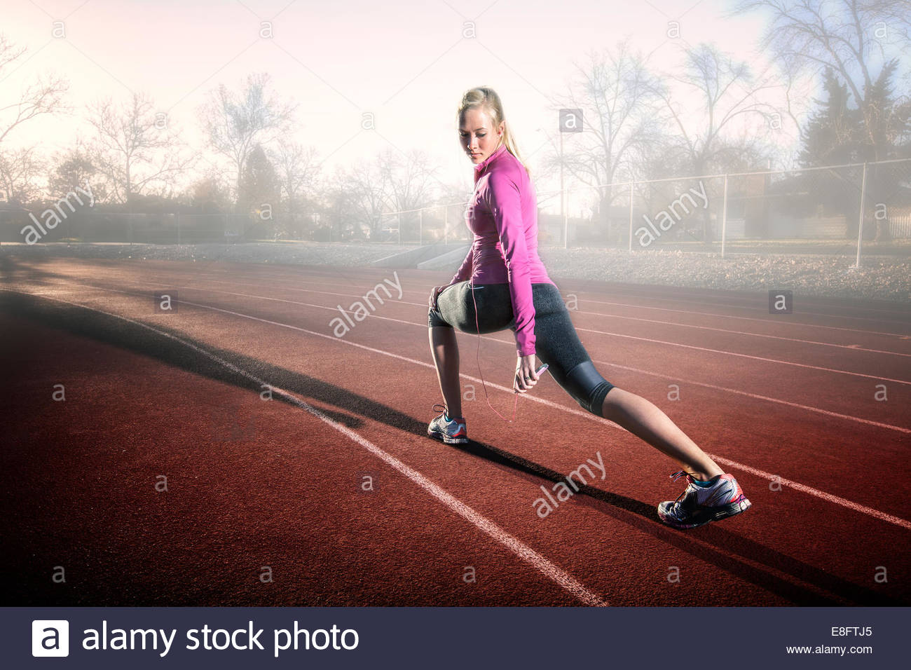 Woman stretching on running track and listening to music, Colorado, America, USA - Stock Image