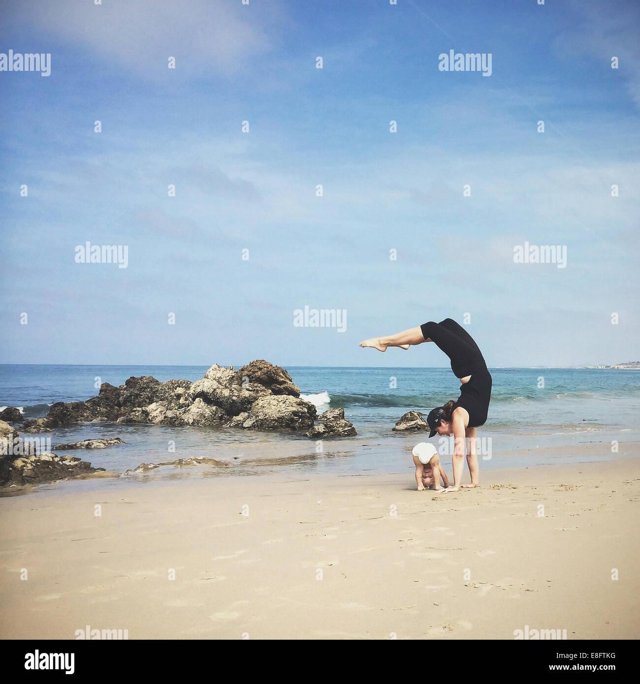 Mother and son doing yoga on beach, California, america, USA - Stock Image