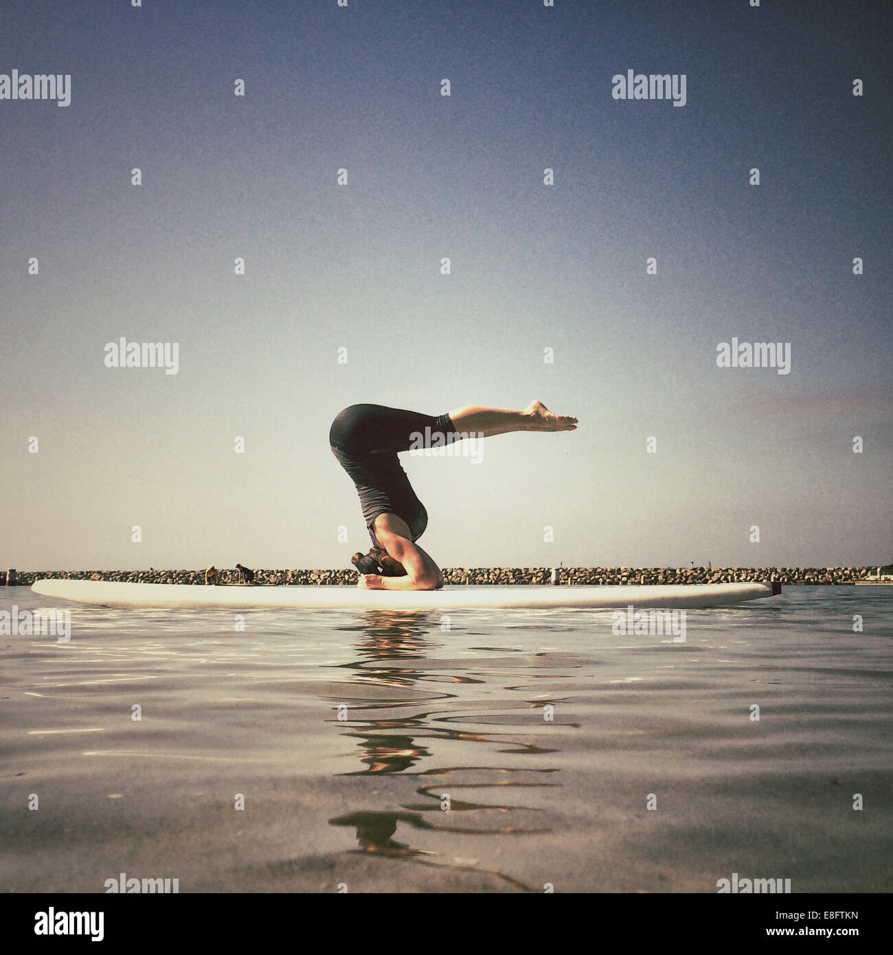Woman doing yoga handstand on surfboard, california, america, USA - Stock Image