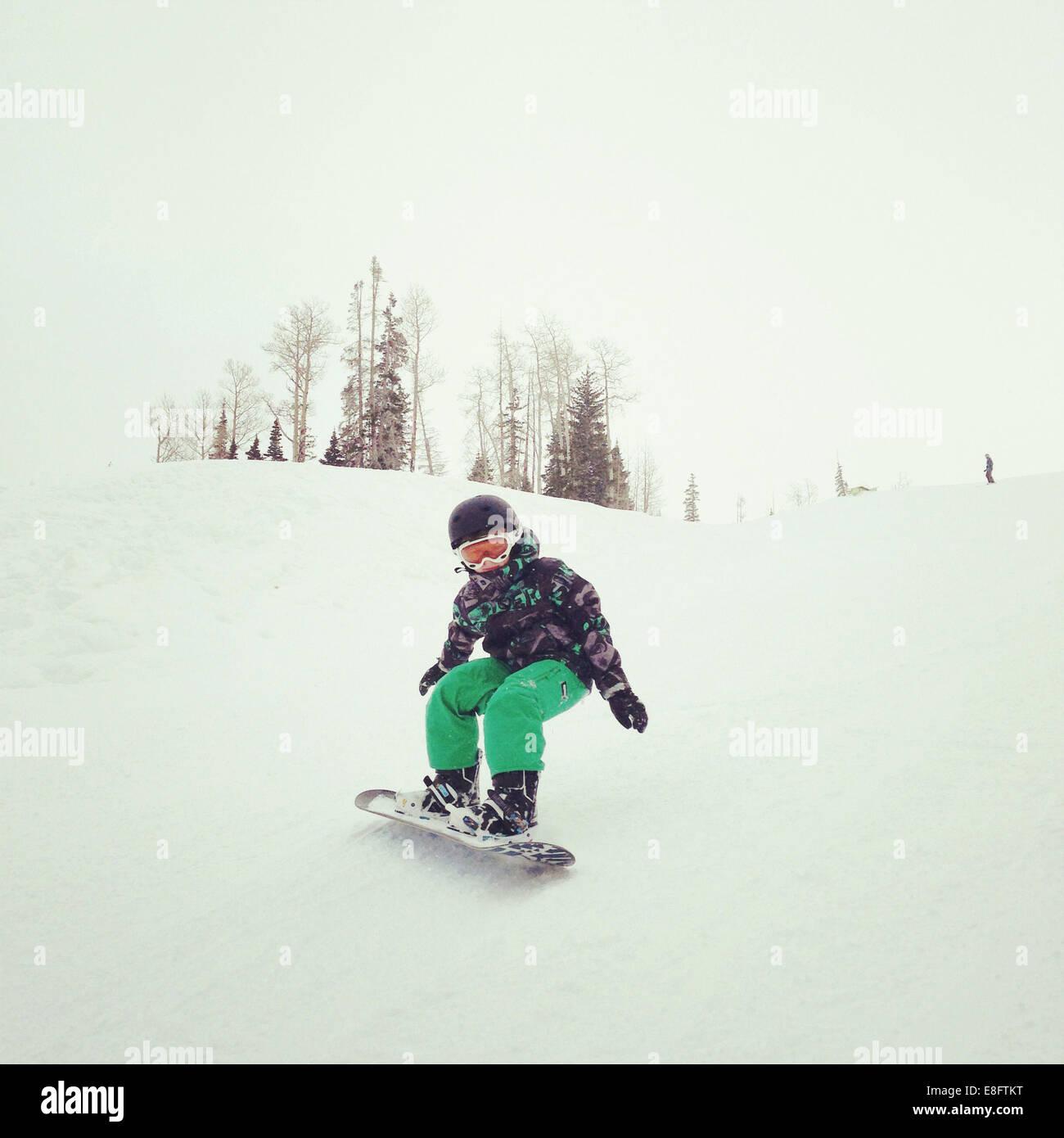 Boy snowboarding down hill - Stock Image