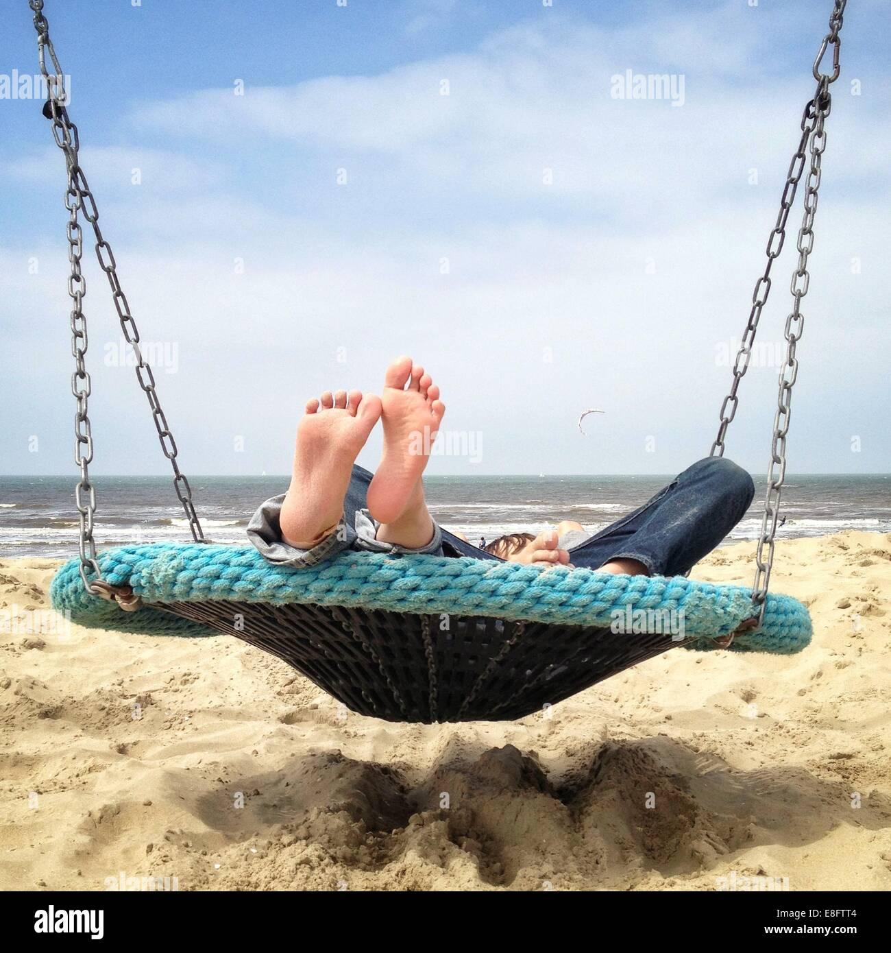 Kids lying in a swing - Stock Image