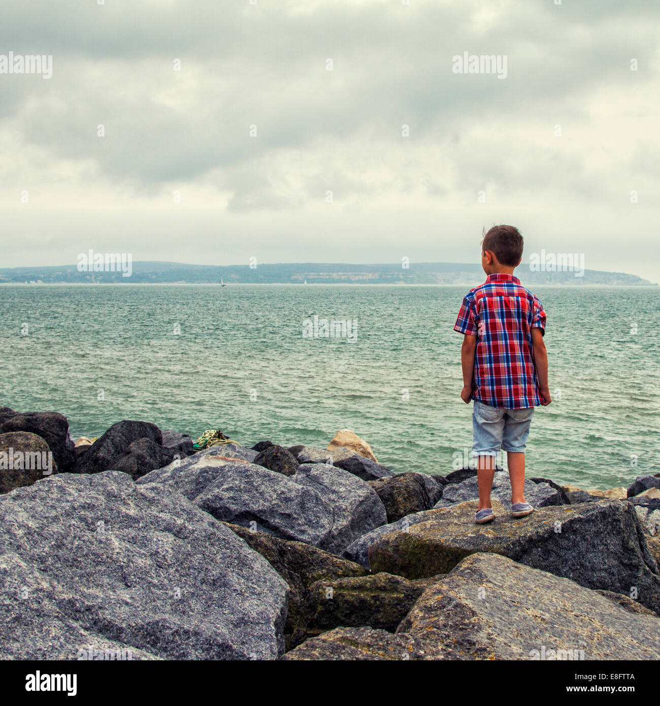 Boy standing on rocks looking at sea - Stock Image
