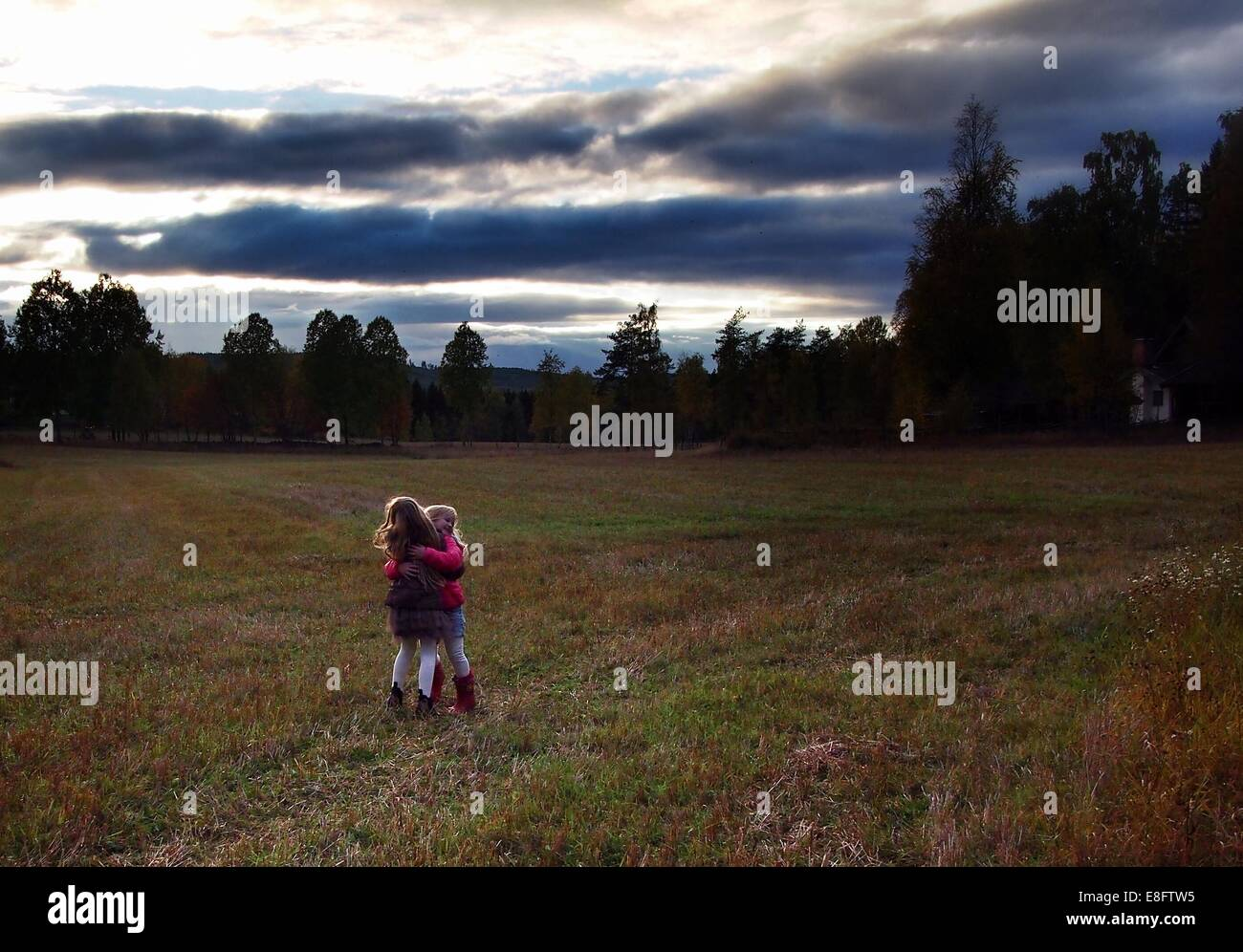 Sweden, Two girls (6-7 years, 8-9 years) hugging outdoors - Stock Image