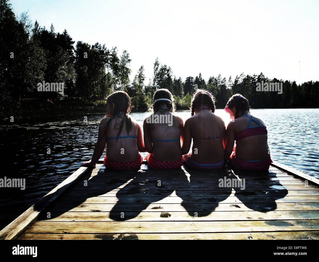 Sweden, Rear view of 4 children sitting on pier (6-7 years, 8-9 years) - Stock Image