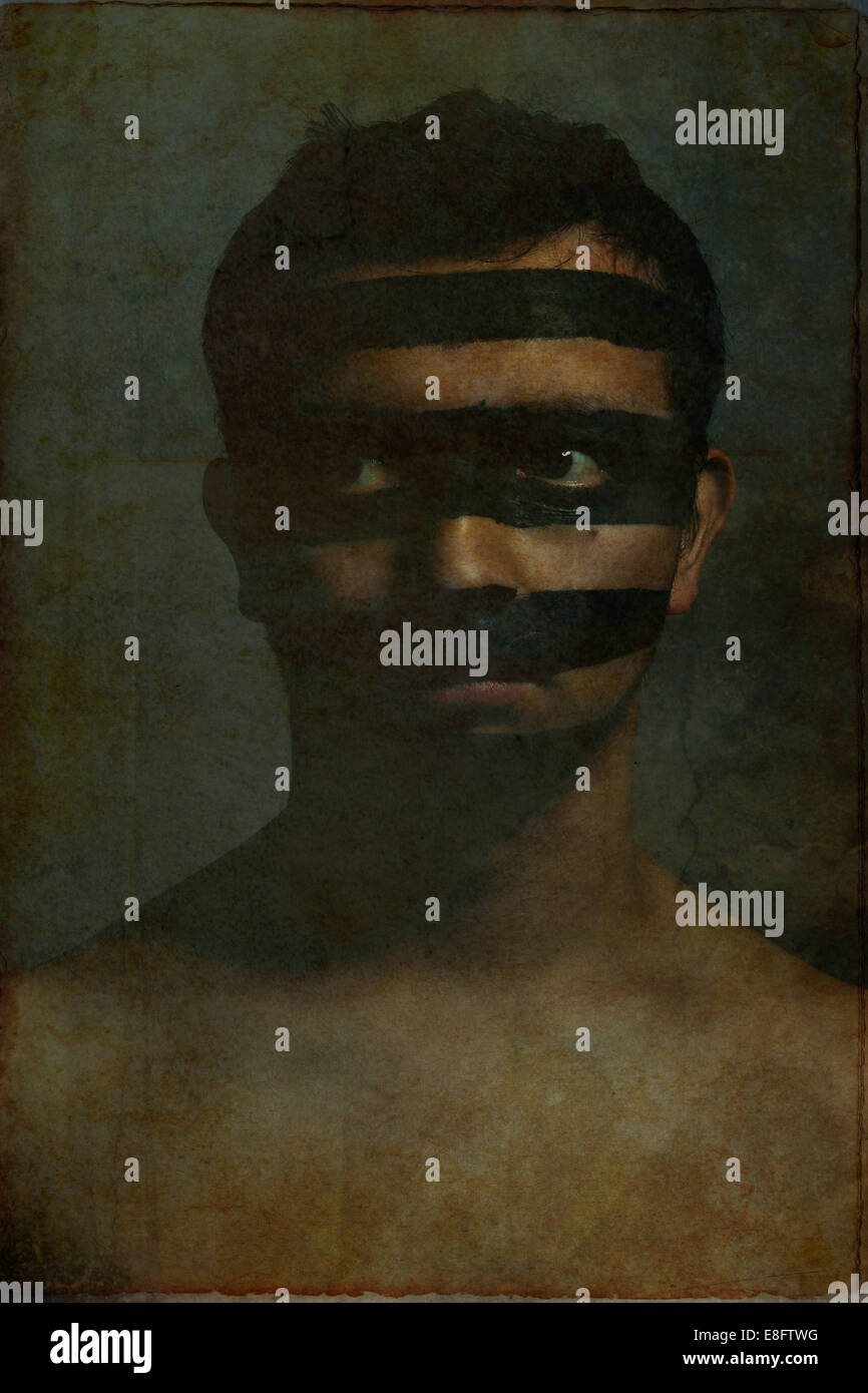 Portrait of young man with black stripes on face - Stock Image
