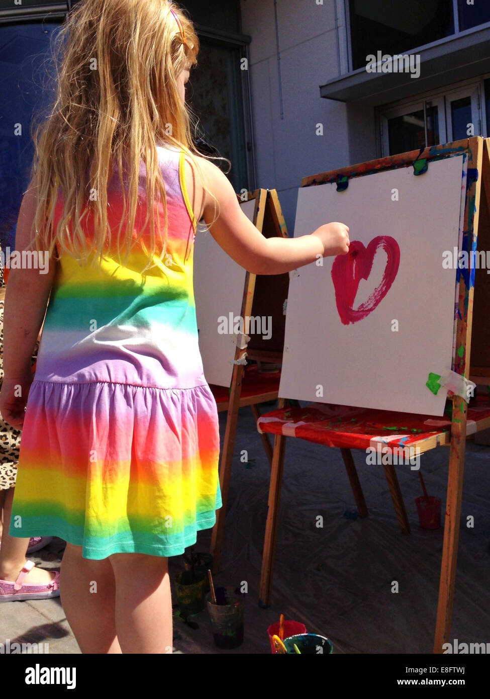 Girl (8-9) painting heart - Stock Image
