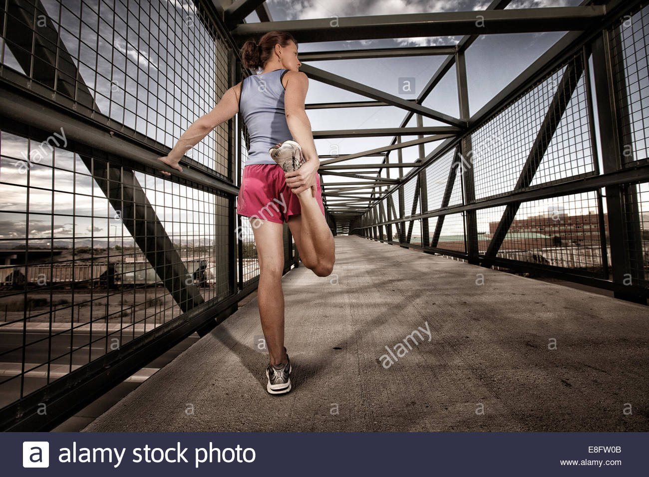 USA, Colorado, Woman runner stretching on bridge - Stock Image