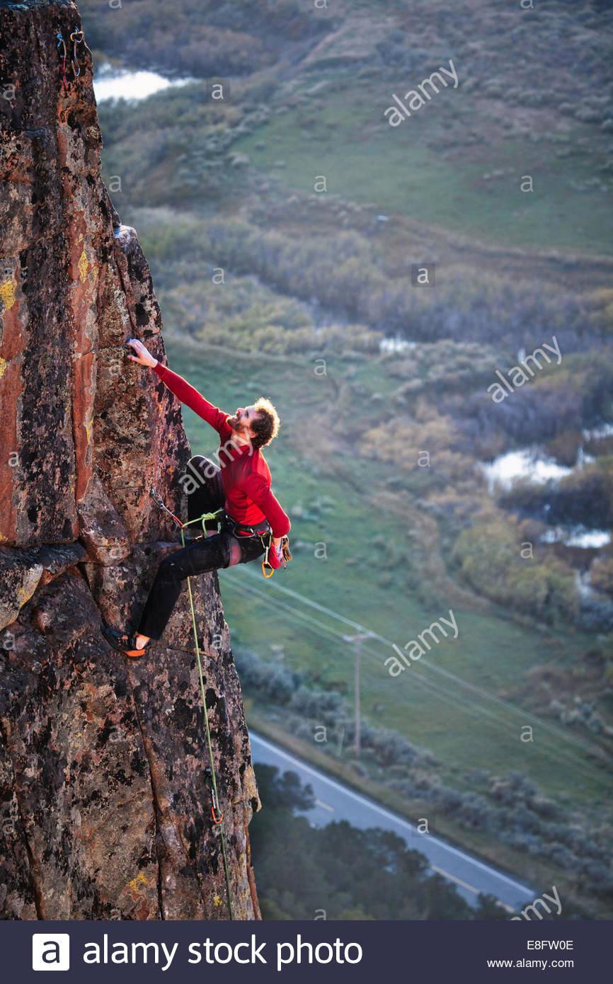 USA, Colorado, Man climbing on sandstone wall - Stock Image