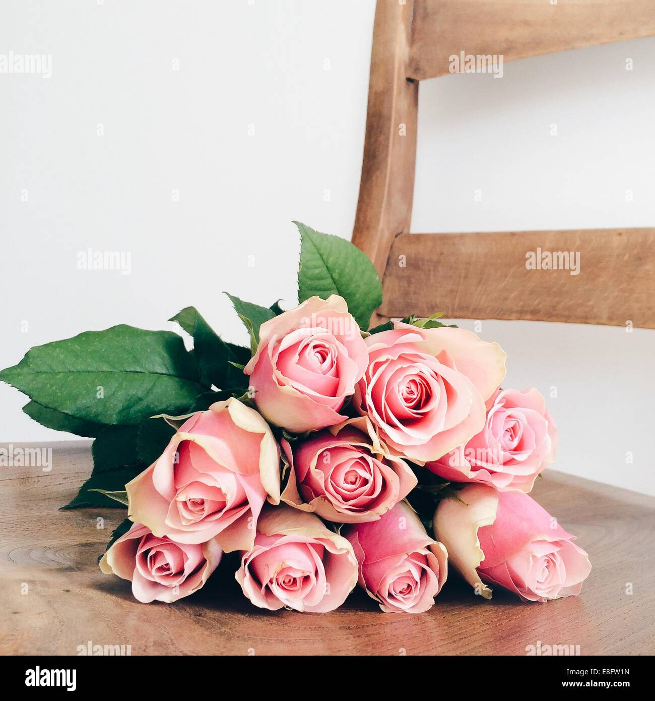 Bouquet of Pink roses lying on chair - Stock Image
