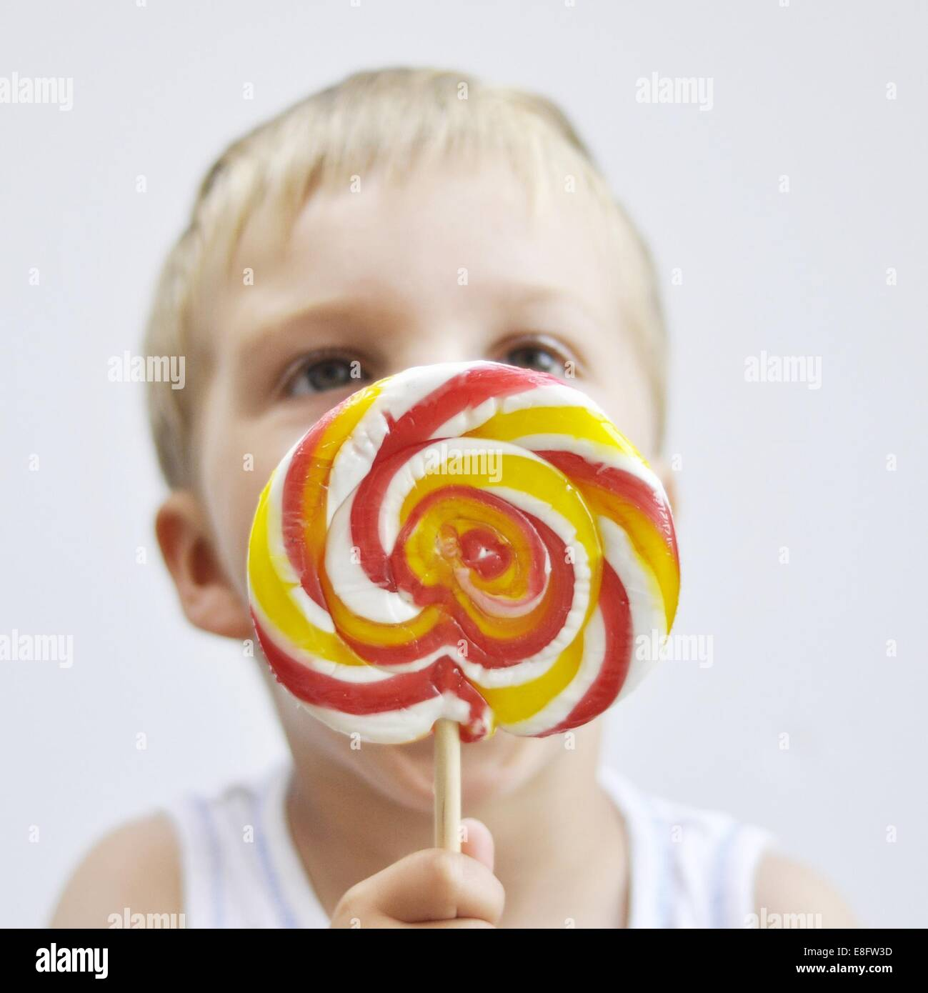 Boy licking a giant lollipop - Stock Image