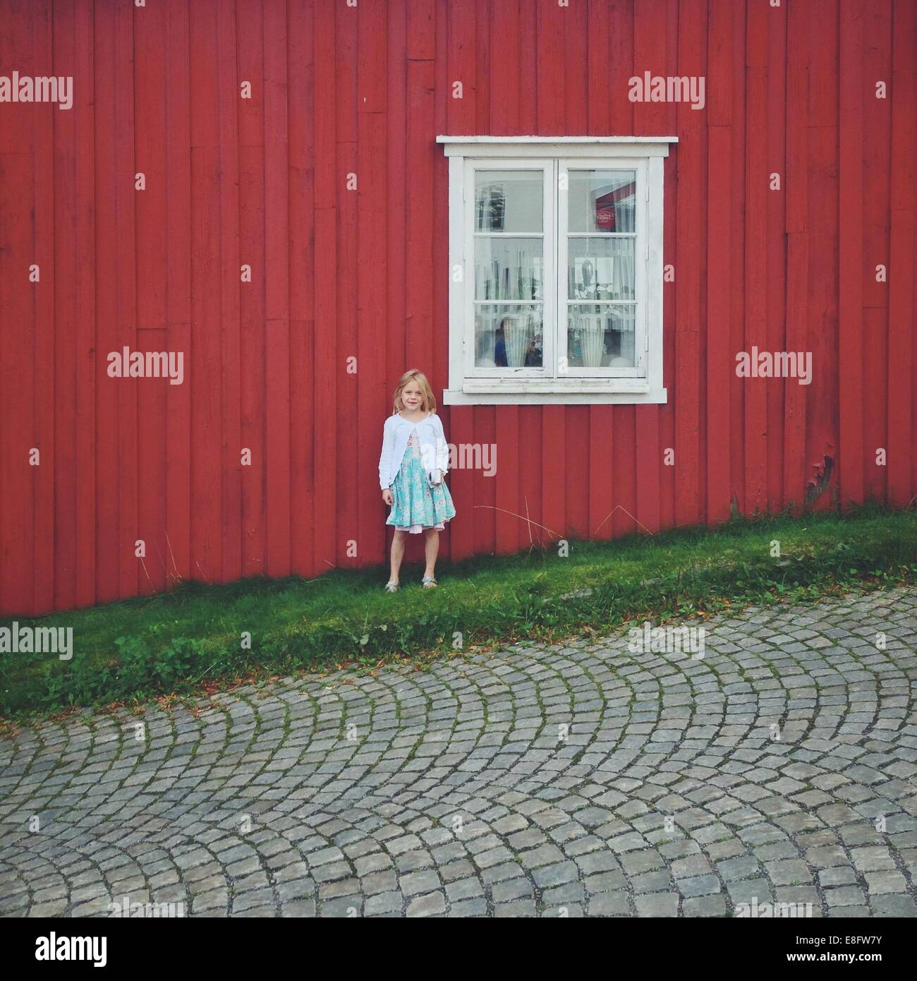 Norway, Girl (12-13) standing against red house - Stock Image