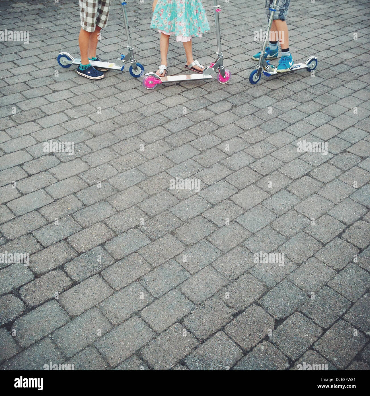 Close up of children (10-11, 12-13) standing next to scooters - Stock Image