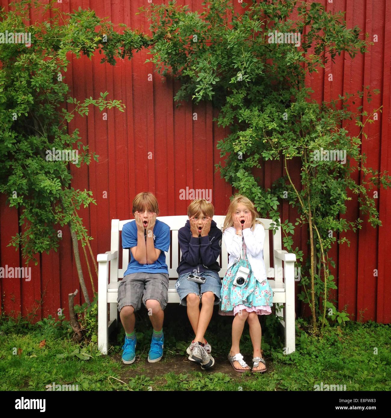 Three children (10-11, 12-13) sitting on bench in garden - Stock Image