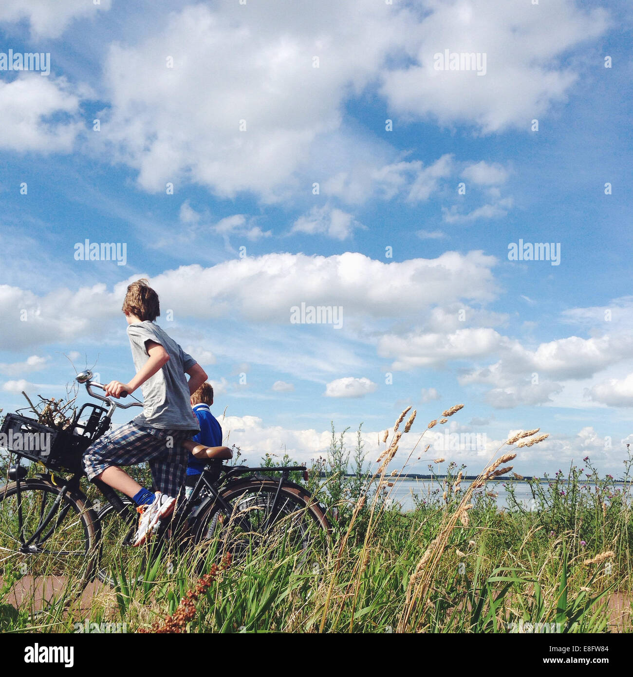 Netherlands, Two boys (10-11) biking near sea - Stock Image