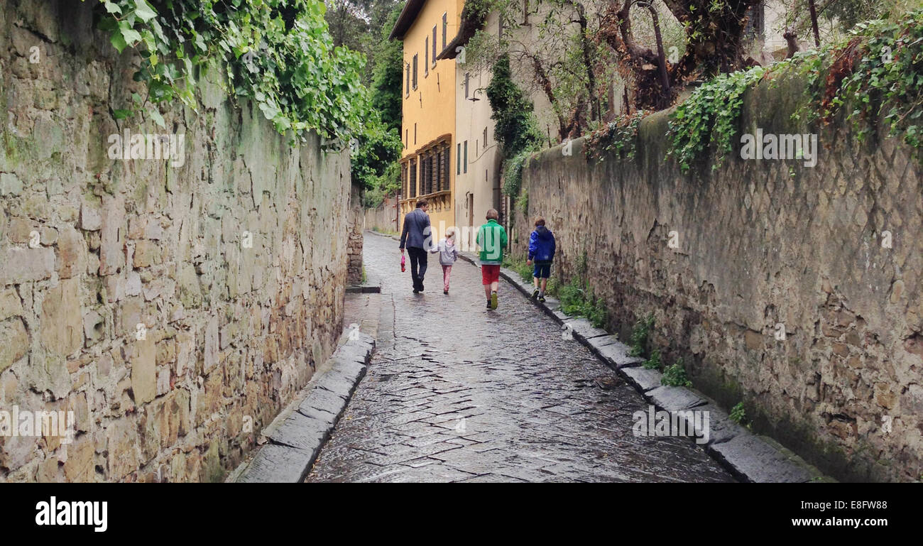 Italy, Tuscany, Florence, Dad with children (8-9), (10-11) on sidewalk - Stock Image