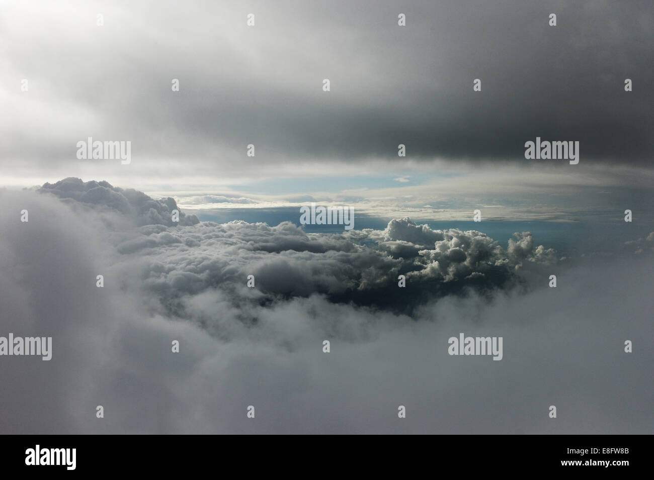 Gap in stormy cumulonimbus clouds showing bright sky - Stock Image