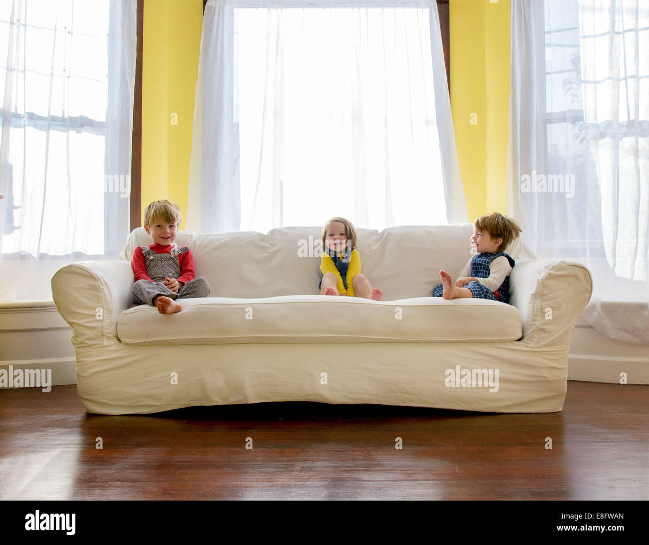 Children ( 2-3, 4-5 ) sitting on sofa - Stock Image