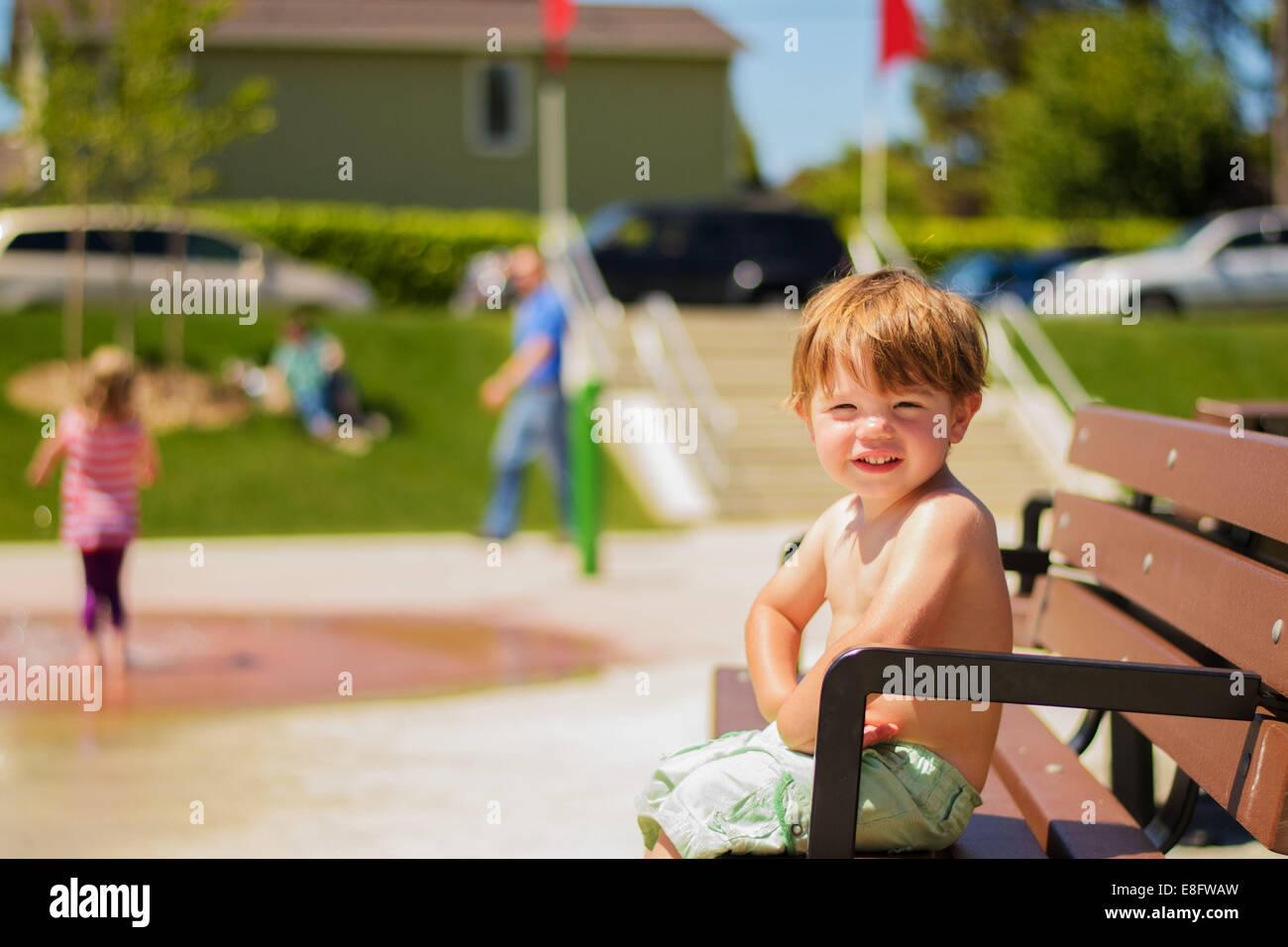 Portrait of boy ( 2-3) sitting on bench - Stock Image
