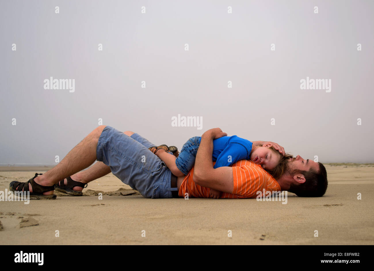 Son ( 2-3 ) lying on father's stomach - Stock Image