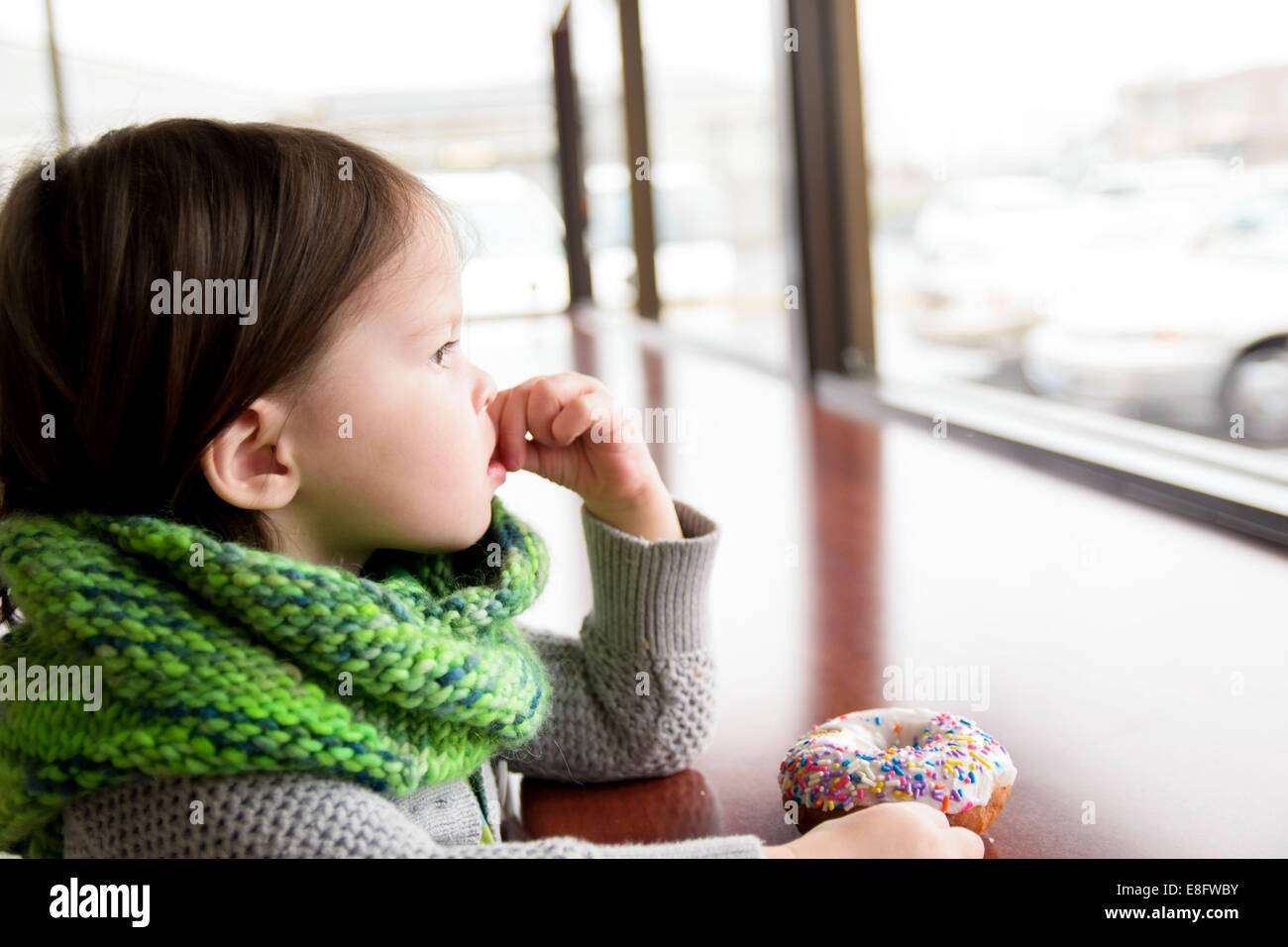 Girl with donut (2-3 years) - Stock Image